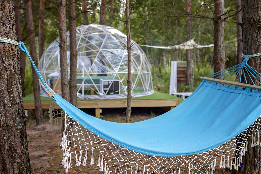 Transparent bell tent with comfortable bed and pillow in forest, glamping hotel, luxury travel, glamourous camping with amenities, dome tent, feel at home in great outdoors lifestyle, selective focus